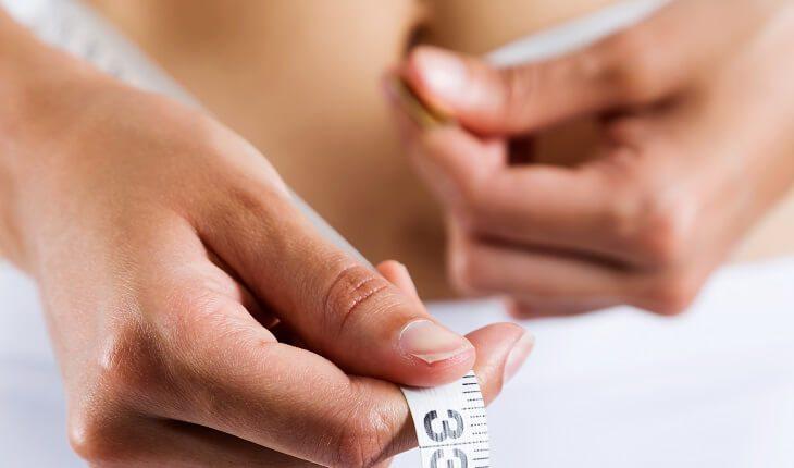 Exercícios podem aumentar os seios e deixá-los mais firmes? Foto de uma fita métrica passada na cintura