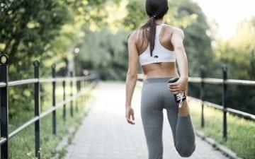 Tendinite no quadril: exercícios e alongamentos para evitar dores. Na foto, uma mulher com roupa de ginástica se alongando.
