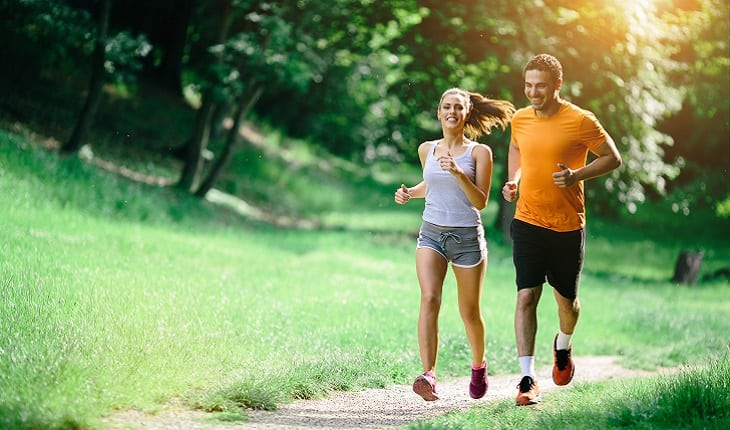 a foto mostra um casal correndo em um ritmo leve em um parque