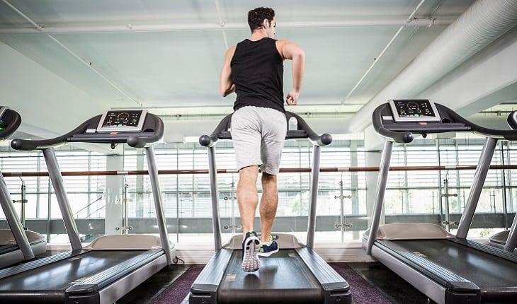 a foto mostra um homem correndo em uma esteira de costas para a câmera