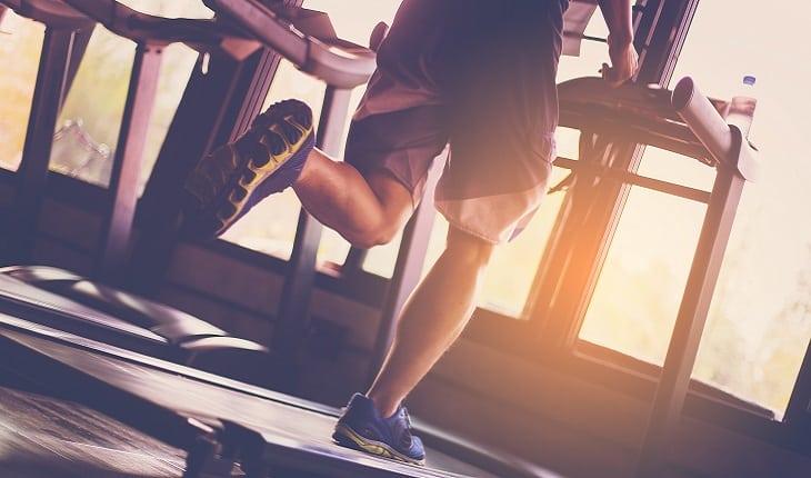 a foto mostra um homem correndo na esteira na academia