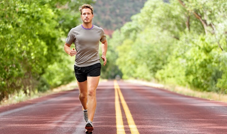 a foto mostra um homem correndo em uma estrada na direção da câmera