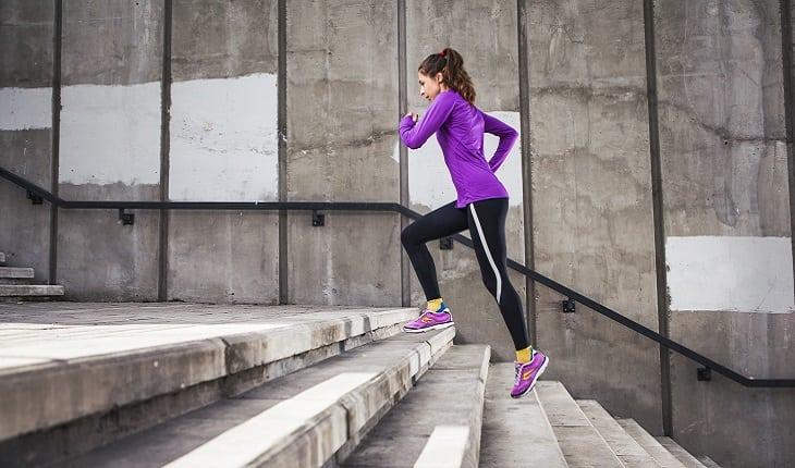 a foto mostra uma mulher com uma blusa lilás subindo uma escada correndo