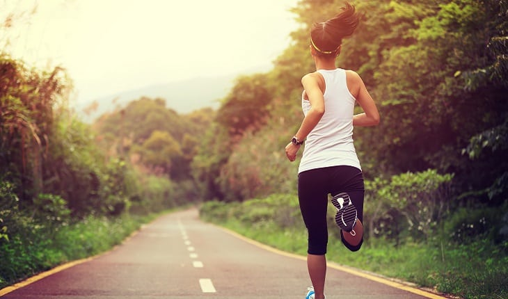 a foto mostra uma mulher correndo em uma estrada