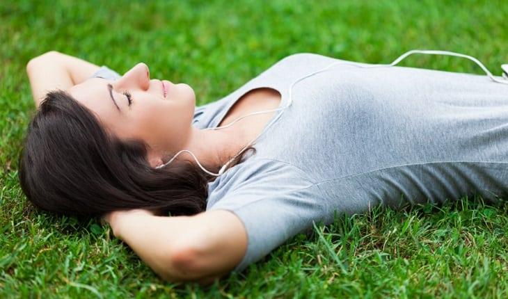 a foto mostra uma mulher deitada em um gramado relaxando
