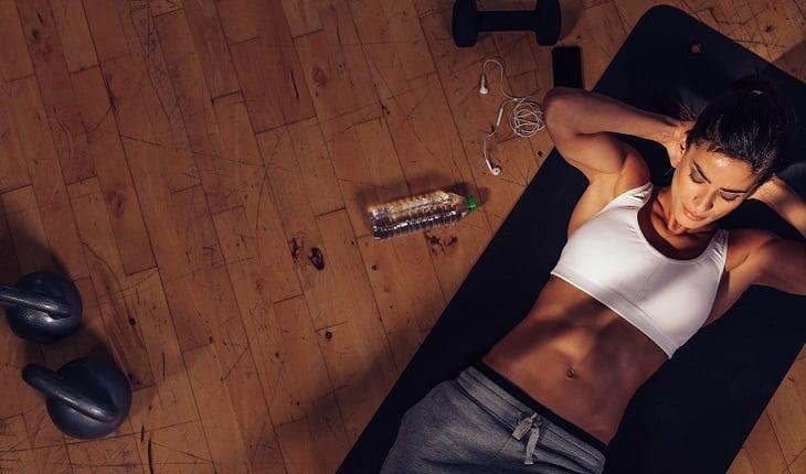 a foto mostra uma mulher deitada no chão fazendo um exercício abdominal