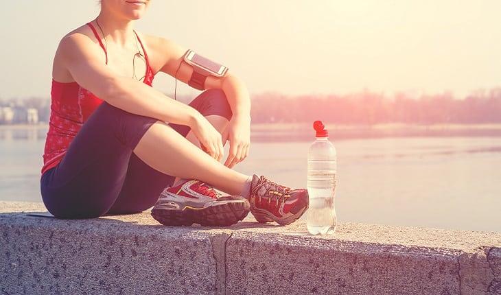 a foto mostra uma mulher sentada em uma mureta com as pernas cruzadas e uma garrafa de água na sua frente