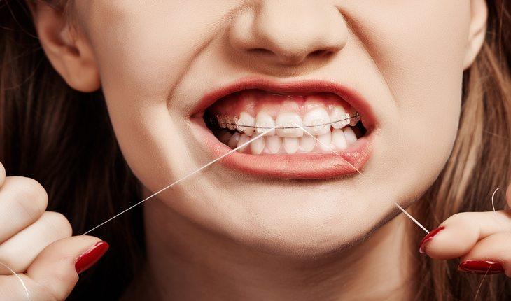 Pessoa passando fio dental Dicas para viver mais