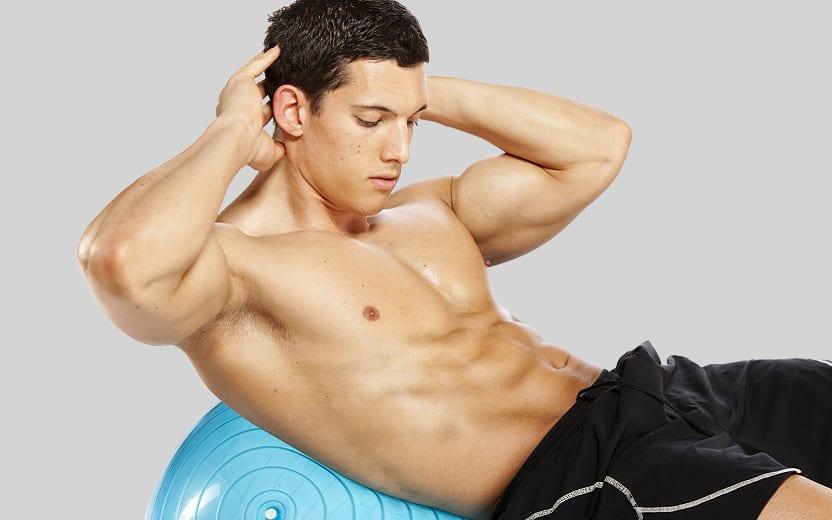 A foto mostra um homem sem camisa fazendo abdominal com as costas apoiadas em uma fitball, um exercício que faz parte da super série funcional de abdominais