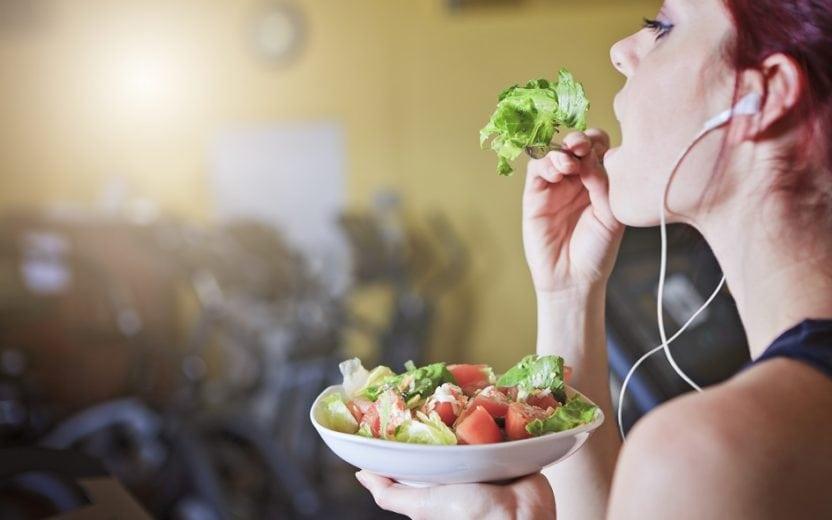 A foto mostra uma mulher comendo alimentos antienvelhecimento na academia