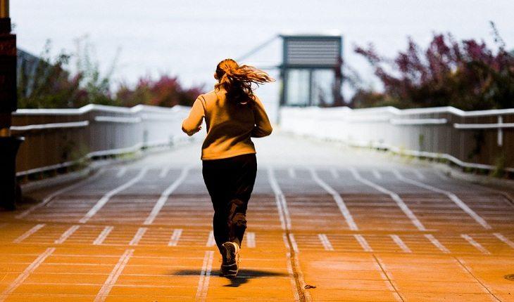 mulher correndo com casaco corredor iniciante
