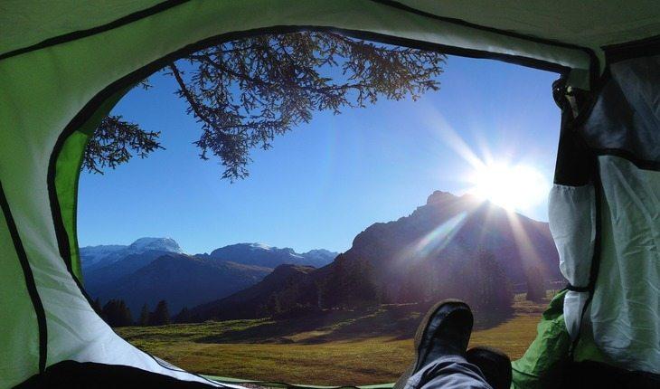 Pessoa dentro de uma barraca observando a vista das montanhas acampar pela primeira vez