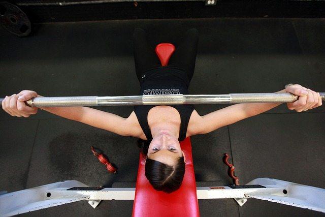 Mulher fazendo levantamento de peso. Descanso entre as séries: qual o tempo ideal para maximizar ganhos?