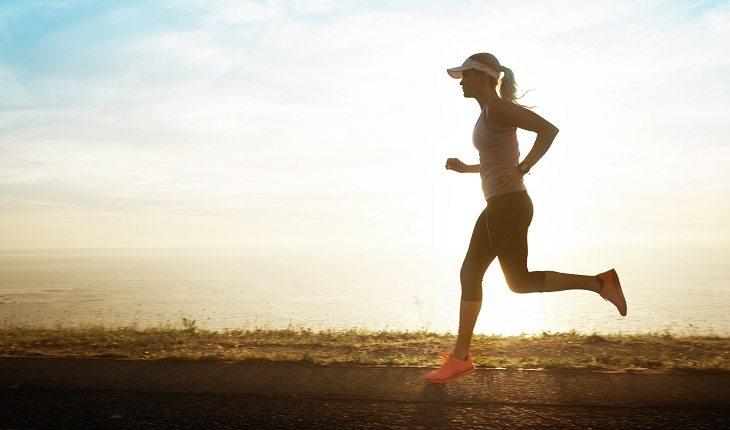 Motivos para a corrida entrar de vez na sua vida: mulher correndo paisagem sol