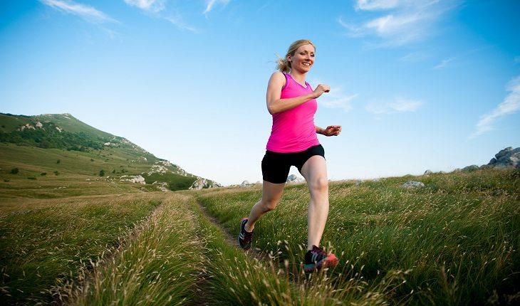Imagem de uma mulher correndo no campo atividade física