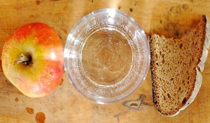 Copo de água, fatia de pão e maçã sobre mesa dicas para reeducar o paladar