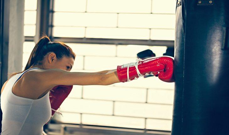 foto de uma moça com luva de boxe, batendo em um saco de pancada