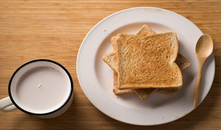 foto de uma xícara de café ao lado de várias torradas, ilustrando um café da manhã