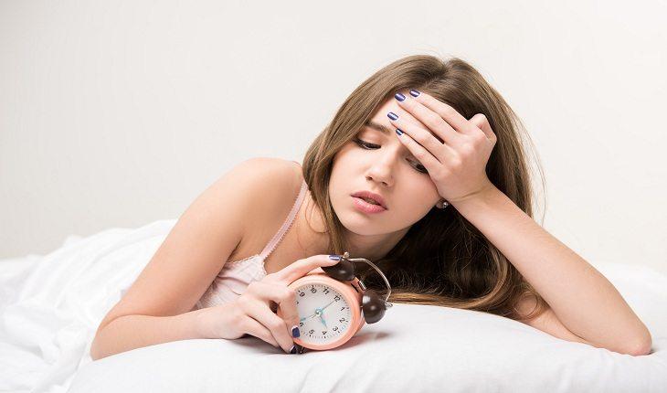 foto de uma mulher na cama, olhando para um relógio