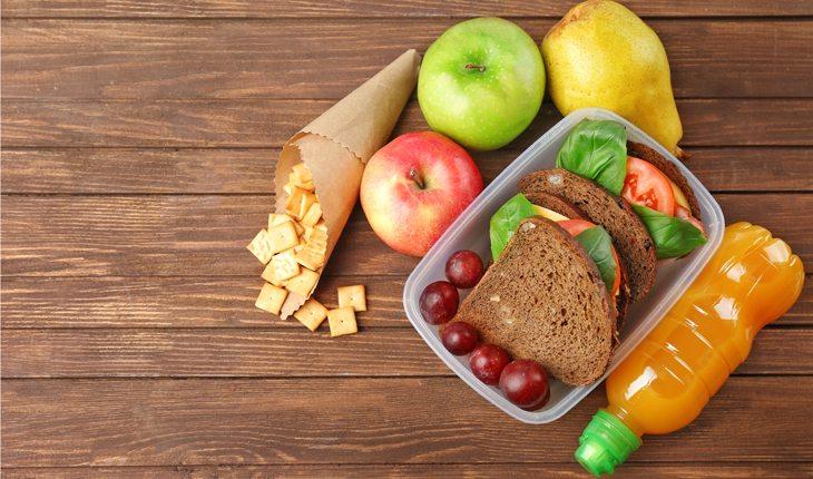Dicas para evitar lesões no joelho: alimentação. Na foto, frutas, como maçã e uva, além de pão integral, para representar uma alimentação saudável.
