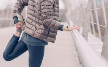 Mulher fazendo alongamento para quem corre antes de começar o exercício