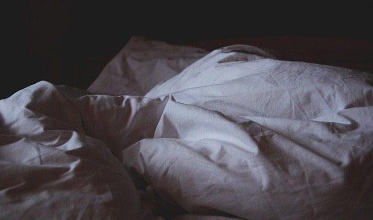 Imagem de uma pessoa deitada em uma cama no escuro Dicas para dormir melhor
