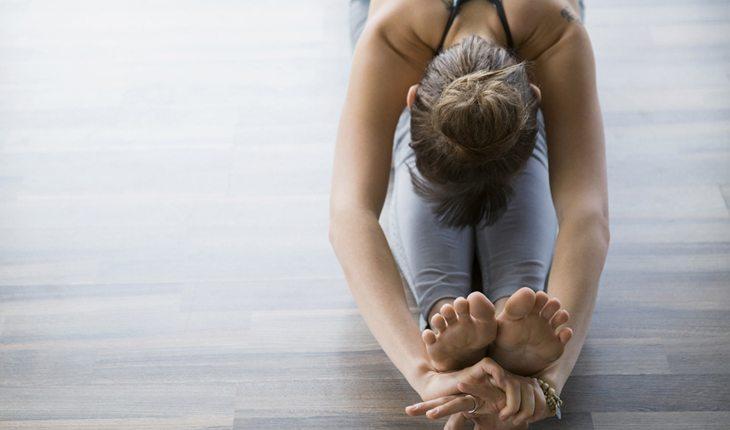 Dicas para evitar lesões no joelho: alongamento. Na foto, uma mulher se alongando.