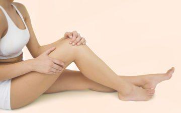 evitar lesões no joelho: mulher sentada com roupa branca, tocando no joelho