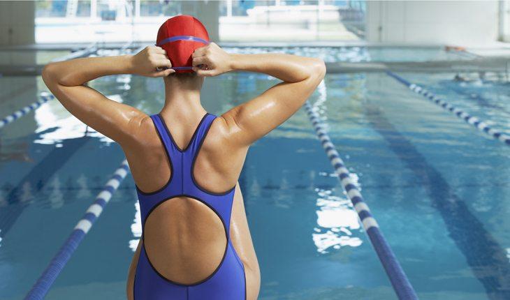 Dicas para evitar lesões no joelho: esportes de baixo impacto. Na foto, uma mulher de costas, de maiô. Ela está de frente para uma piscina, representando a natação.