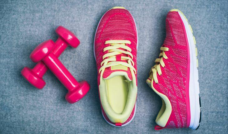 Dicas para evitar lesões no joelho: escolha o tênis certo. Na foto, um par de tênis rosa com verde e pesos rosas.