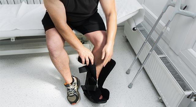 Homem com o pé machucado usando bota ortopédica