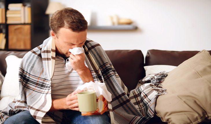 homem gripado, assoando o nariz, sentado em um sofá. Atividade física na terceira idade