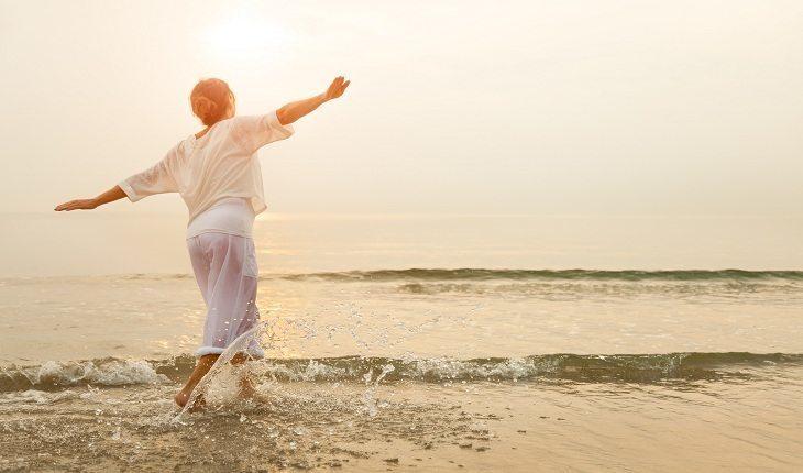 Mulher idosa em uma praia. Atividade física na terceira idade