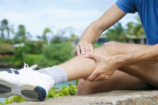 Homem com lesão na perna sentindo dor