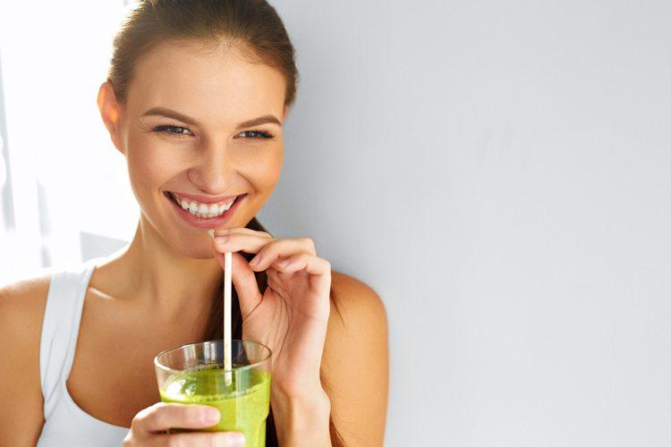 Mulher rindo e tomando suco verde
