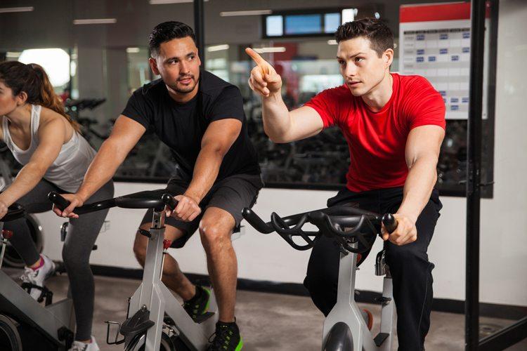 Homens irritados na academia, fazendo bicicleta
