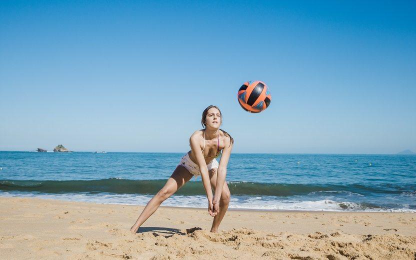 Esportes e atividades para praticar na praia: vôlei. Na imagem, uma jovem está na praia posicionada para uma manchete na bola de vôlei
