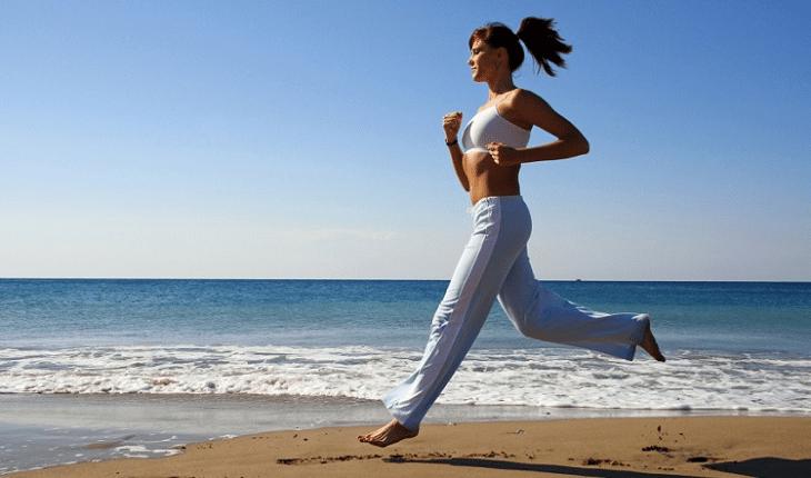 Mulher com roupa branca correndo na beira do mar