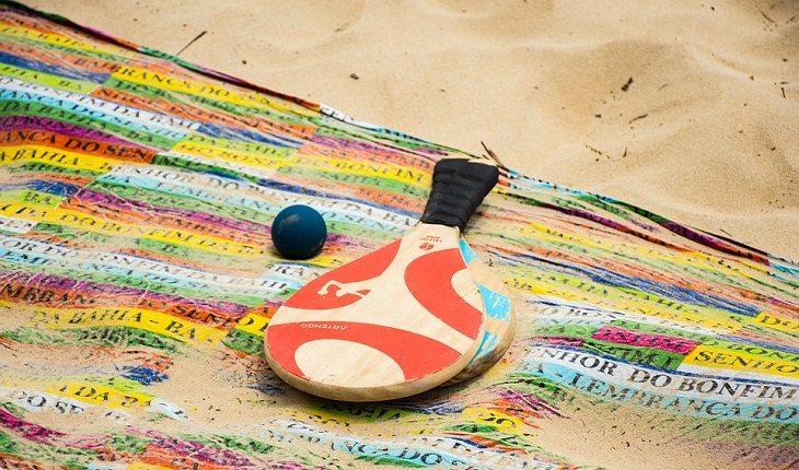 Raquetes de frescobol na areia ao lado de uma bola