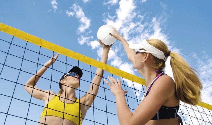 Mulheres em disputa na rede, jogando vôlei de praia