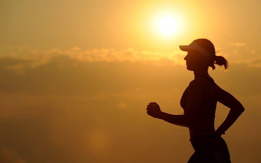 Mulher praticando sua corrida no fim de tarde após os 10 motivos para correr