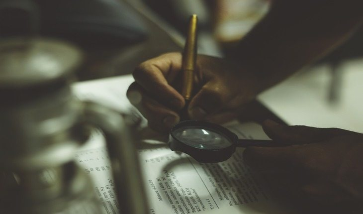 pessoa lendo um livro com uma lupa dicas para-se preparar para uma prova