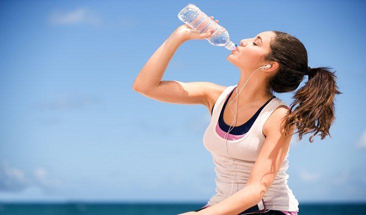 Mulher andando de bicicleta e bebendo água Férias