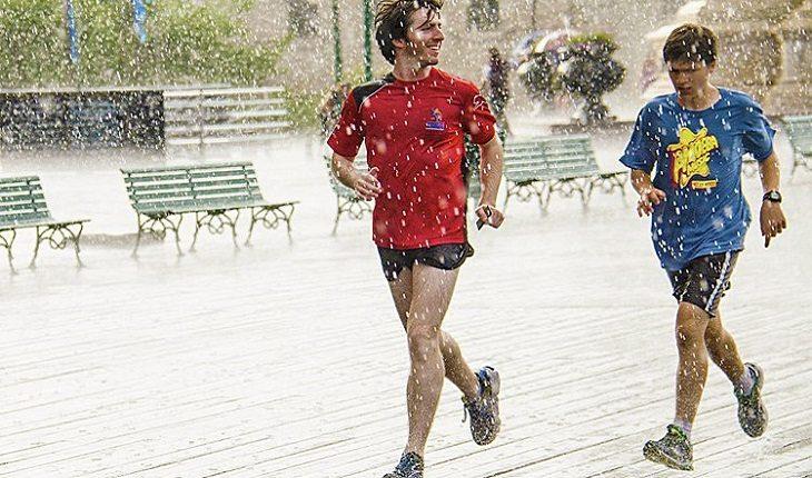 a foto mostra duas pessoas correndo uma maratona sob a chuva