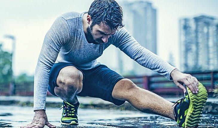 homem alongando a perna antes de sair para correr na chuva