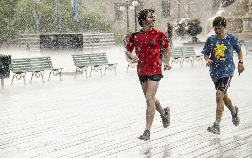 a foto mostra duas pessoas participando de uma maratona sob chuva, ilustrando como correr na chuva