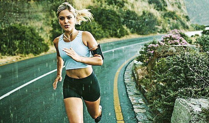 a foto mostra uma mulher correndo em uma estrada sob chuva