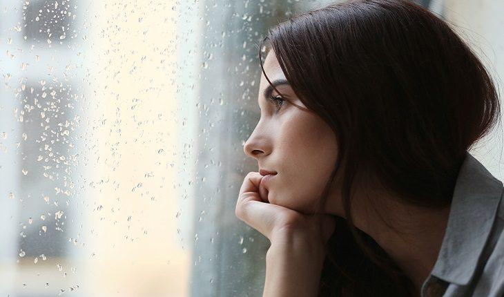 a foto mostra uma mulher observando a chuva pela janela