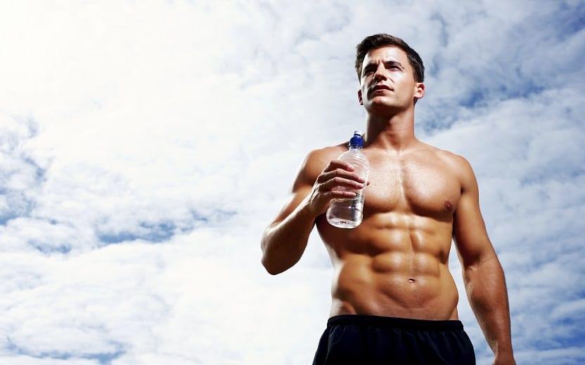 Homem forte segurando uma garrafa na mão tomar água