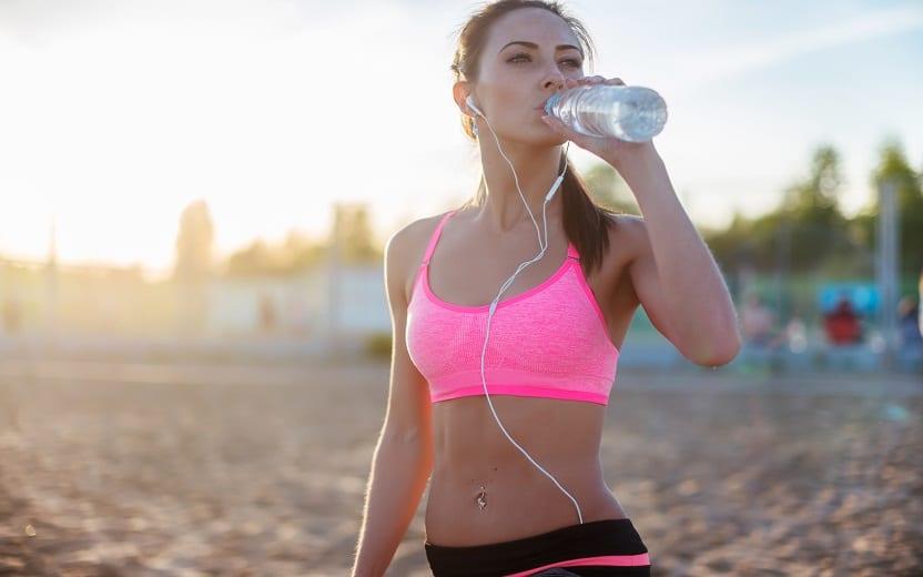 mulher em uma praia usando fones de ouvido e bebendo água tomar água